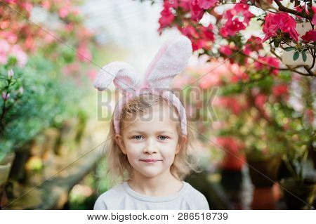 Cute Funny Girl With Easter Bunny Ears At Garden. Easter Concept. Laughing Child At Easter Egg Hunt.