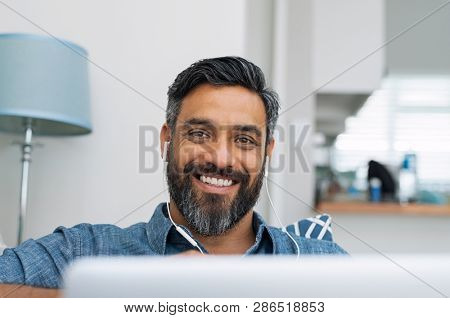 Portrait of happy man using laptop with earphones while lying on couch. Casual man in video call lying on sofa with computer. Mature middle eastern man with earbuds looking at camera with a big smile.