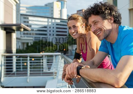 Couple of runners resting while training. Mature woman and man having a rest and smiling while looking away in city. Cheerful healthy couple resting on railing fence after morning exercise routine.