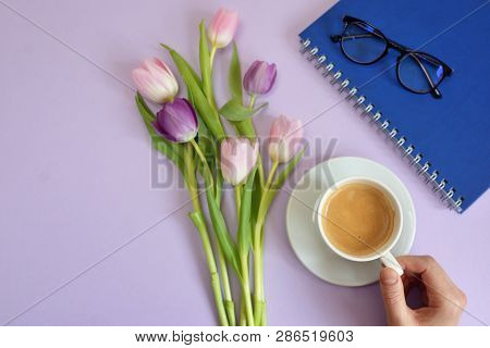 Woman Hands And Cup Of Coffee And Tulips