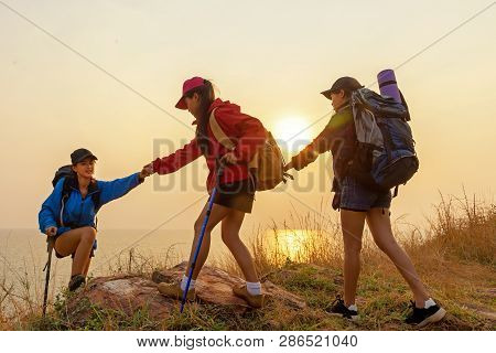 Group Hiker Team Woman Helping Her Friend Climb Up The Last Section Of Sunset In Mountains. Traveler