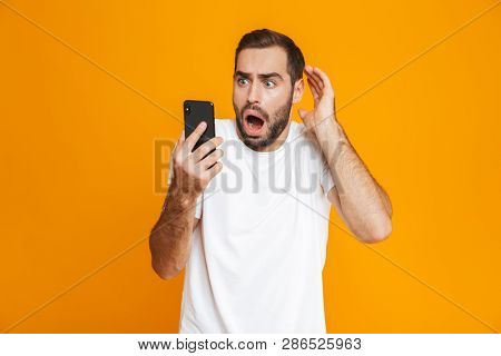 Photo of terrified man 30s in casual wear looking at mobile phone with fear isolated over yellow background poster