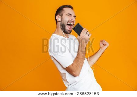 Photo of handsome man 30s singing while using earphones and mobile phone isolated over yellow background poster
