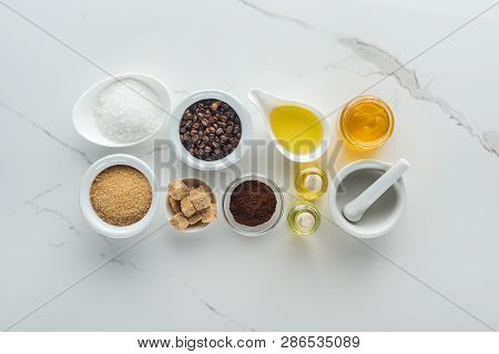 Flat Lay Of Bowls With Natural Cosmetic Ingredients, Cosmetic Bottles And Pounder On White Surface