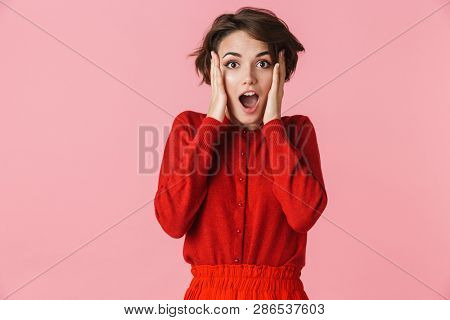Portrait of an excited beautiful young woman wearing red clothes standing isolated over pink background