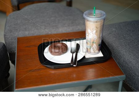 Chocolate Doughnut Served With A Personnel Glass Of Coffee. Reduce Using The Plastic Glasses By Brin