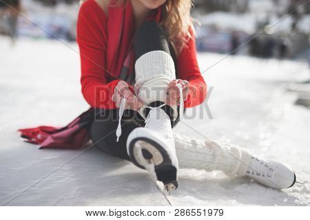 Woman Tie Shoelaces Figure Skates At Ice Rink Close-up