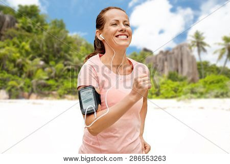 fitness, sport and healthy lifestyle concept - smiling woman with earphones wearing armband for smartphone, running and listening to music over tropical beach on seychelles island background poster