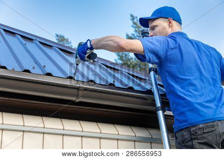metal roofing - roofer working on the house roof poster