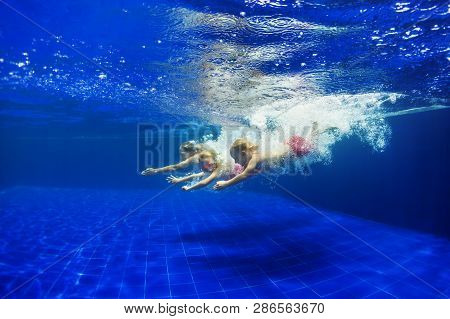 Happy Family - Mother, Kids Learn To Swim, Dive Underwater With Splashes. Jump With Fun In Swimming