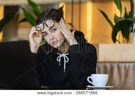 Portrait Of Tired Shortcut Hipster Girl Sitting With Laptop At The Cafe Interior