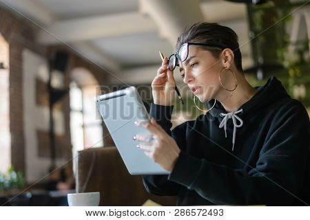 Hipster Shortcut Student In Stylish Optical Spectacles Sitting At Wooden Table In Cafeteria With Cup
