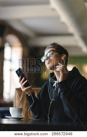 Shortcut Hipster Girl Wearing Glasses Drinking Coffee And Listening Music While Sitting At The Cafe