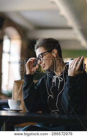 Shortcut Hipster Girl Wearing Glasses Resting In Coffee Shop And Listening Favorite Music In Headpho
