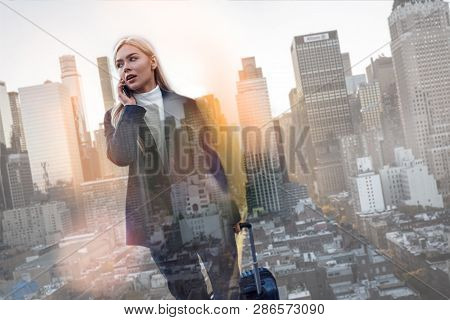 Business Trip. Beautiful Young Business Woman Carrying Luggage And Talking By Phone While Standing A