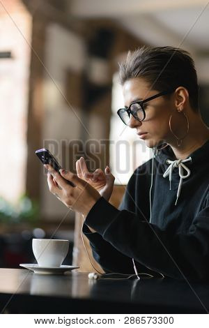Shortcut Hipster Girl Wearing Glasses Turn On Music On The Smartphone While Sitting At The Cafe
