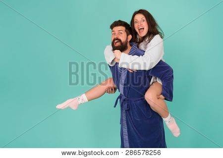 Enjoying Every Second Together. Handsome Young Man Piggybacking Beautiful Woman. Couple In Bathrobes