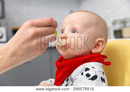 Mother Is Feeding Baby Boy With Spoon. Healthy Baby Food At Home