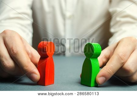 A Man Holds In His Hands The Red And Green Figures Of People Facing Each Other. Conflict Resolution,