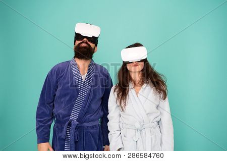 Awakening from virtual reality. Couple in bathrobes wear vr glasses. Conscious awakening. Return to reality. Man and woman explore vr. VR technology and future. VR communication. Exciting impressions. poster
