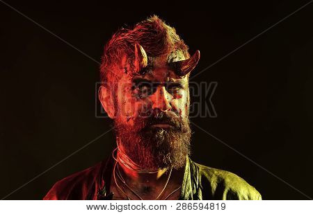 Halloween holiday celebration, cosplay. Satan with beard, red blood, wounds on face. Devil with bloody horns on head. Hell, death, evil, horror concept. Man demon on black background. poster