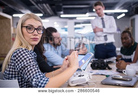 blonde business woman with her multiethnic startup business team discussing new business plan,working on laptop and tablet computer while learning about drone technology for future business ventures