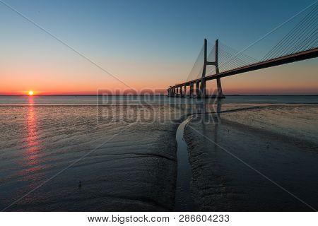Peaceful Atmosphere At Vasco Da Gama Bridge In Lisbon During Sunrise. Ponte Vasco De Gama, Lisboa, P