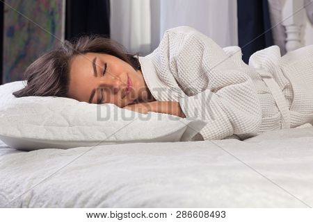 Young Beautiful Brunette Woman Wearing White Bathrobe Sleeping In The Bed And Relaxing In The Mornin