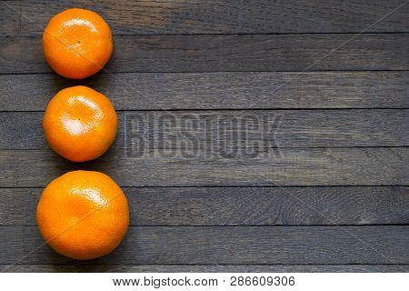 Three Sweet Bright Orange Tangerines On Dark Brown Wooden Table With Copy Space. Close Up, Top View,