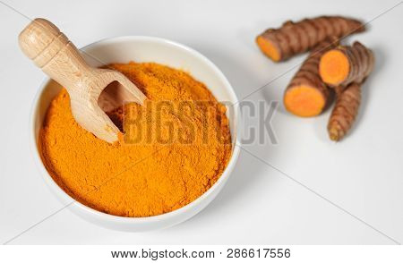 Turmeric Powder And Roots Healthy Spice Asian Food With Sliced Turmeric Roots And Powder In A Bowl W