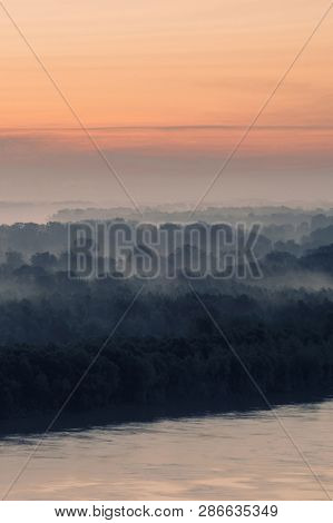 poster of Mystical view on riverbank of large island with forest under haze at early morning. Eerie mist among layers from tree silhouettes. Morning atmospheric landscape of majestic nature in blue faded tones.