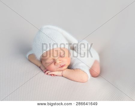 Cute little baby in white hat and knitted suit sweetly sleeping