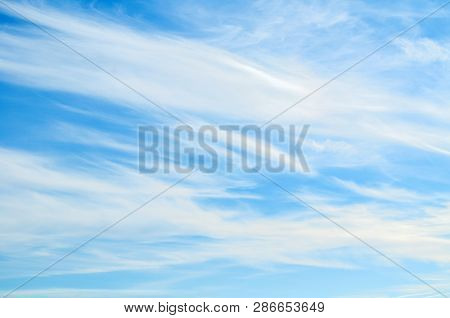 Sky background - dramatic sunset clouds lit by evening sunset light, evening sky scene. Colorful sky landscape, vast sky with fluffy clouds. Sunset sky landscape