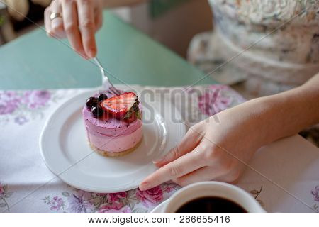 Woman Eating A Cake In A Cafe. Cake With Strawberries And Currants.