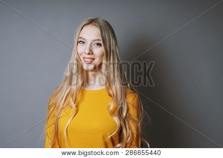 Teenage Girl With Very Long Blond Hair And Beaming Smile Against Gray Background With Copy Space