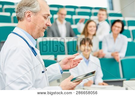 Senior medicine lecturer with tablet training doctors in university lecture hall