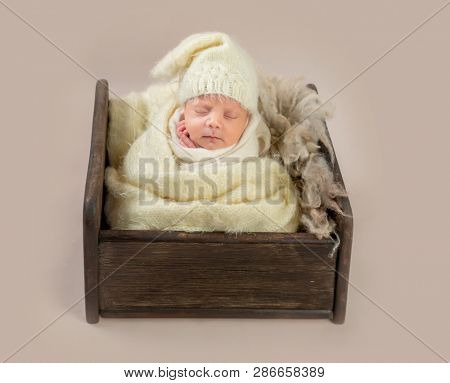 Cute little baby in hat sweetly sleeping in small bed covered in blanket