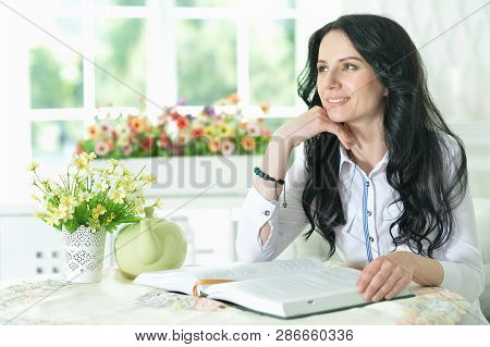 Portrait Of Eautiful Young Woman Sitting At Table