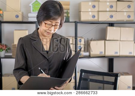 Old Asian Woman Check List Orders Online Customers In The Homeoffice. Concept For Home Base Business