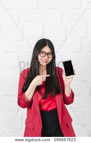 Young Attractive Asian Woman, Wearing Glasses, Long Black Hair In Red Suit Point Finger At The Smart