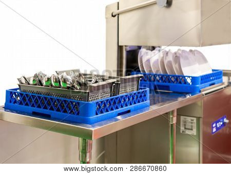 Close Up Spoon And Fork On Basket In Automatic Modern Dishwasher Machine For Industrial Isolated On