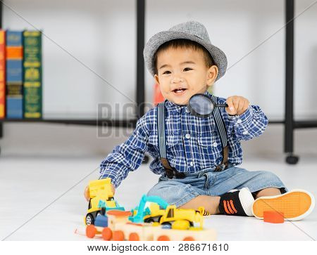 One Year Old Asian Baby Boy Smile And Sitting On Floor Holding To The Magnifying Glass Play The Toys