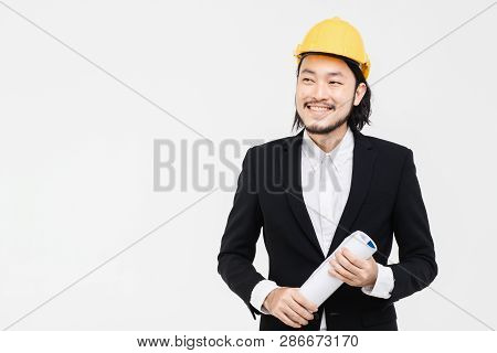 Portrait Of Engineer, In Black Suit, Yellow Helmet On His Head, Standing, He Looking At The Side, Bl