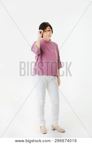 Full Length Portrait Of Aged, Senior Asian Woman, Short Hair, Wearing Glasses, In Casual Fashion, St