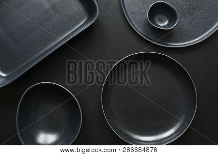 Crockery, clayware, black utensils and different stuff on black tabletop. View from above. poster