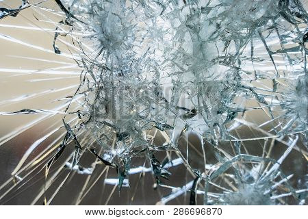 A Heavily Damaged Window Pane With Large Shards And Cracks. Maybe Even Shot On It And It Consists Of