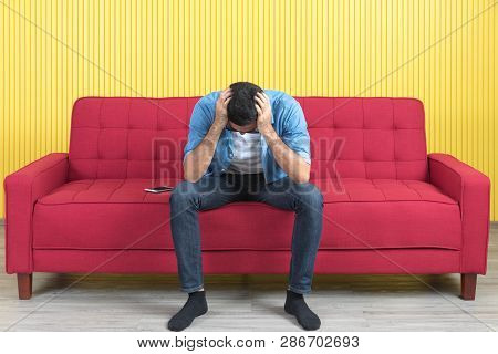 Portrait Of Young Asian Man, In Denim Shirt, Sitting On Red Sofa, Putting His Hand On His Head, Suff
