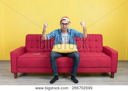 Young Asian Handsome Bearded Man, Wearing Eyeglasses, Santa Hat, In Denim Shirt, Sitting On Red Sofa