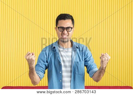 Close-up Shot Of Young Asian Handsome Bearded Man, Wearing Eyeglasses, In Denim Shirt, Pointing And