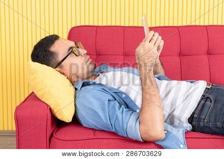 Young Asian Handsome Bearded Man, Wearing Eyeglasses In Denim Shirt, Sprawled Out On Red Sofa, Serio
